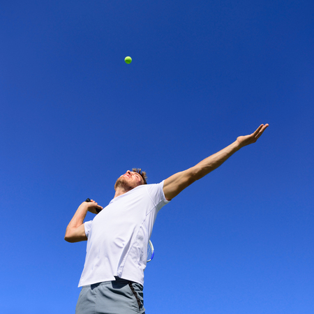 Tennis player man doing serve in position to hit ball in the air. Playing tennis outdoors on blue sky summer background. Active sport athlete doing fitness fun.