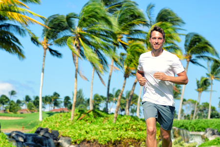 Happy jogging man running in tropical summer park with palm trees in background. Summer active lifestyle healthy young runner training outdoors. Stock Photo
