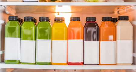Juice bottles for detox cleanse juicing diet- Healthy food online delivery at home in fridge. Selection of many cold pressed vegetables and fruits juices, orange, lemon, beets, spinach, almond milk.