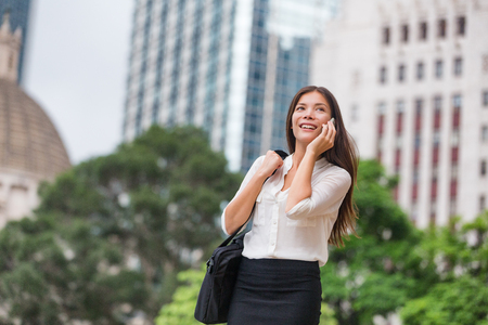 Asian business woman talking on phone walking commute to work office in Hong Kong city. Young businesswoman on smartphone happy. Multiracial Chinese Asian Caucasian female professional outside. Stock Photo