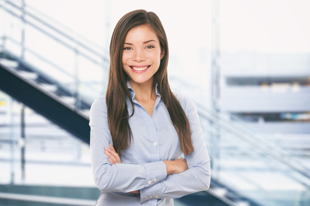 Asian businesswoman smiling on office background. Portrait of multiracial woman in business. Stock Photo
