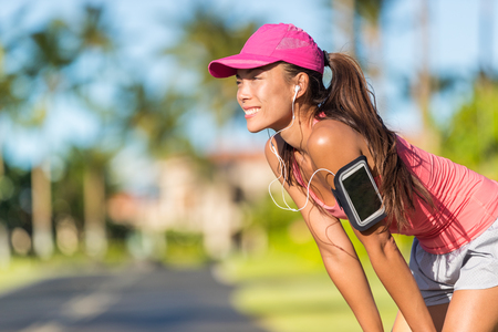 Happy summer running woman runner listening to music on phone sports armband with touchscreen and headphones earphones on city street, active lifestyle. Fitness Asian girl ready for jogging. Stockfoto