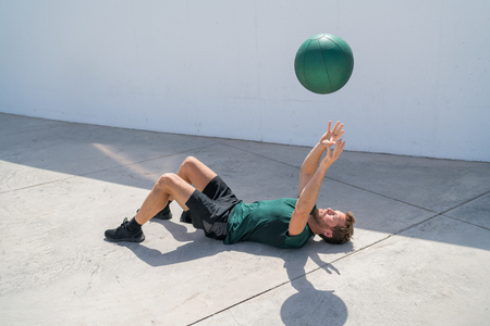 Strength training fit man cross training throwing medicine ball in the air for bench press arm workout exercises using heavy weight ball. Fitness athlete exercising on gym floor. Stock Photo