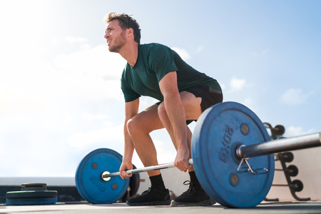 Weightlifting fitness man bodybuilding or powerlifting at outdoor gym. Bodybuilder doing barbell weight workout deadlift with heavy bar.