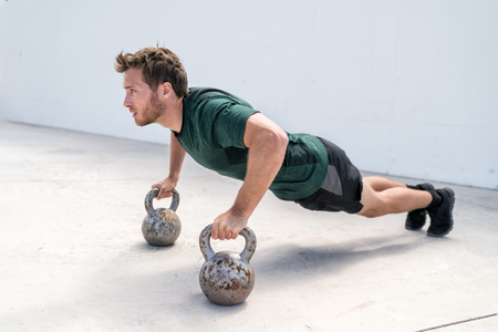 Fitness man strength training body core doing push-ups holding on kettlebells bodyweight floor exercises at outdoor gym.