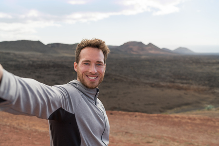 Travel tourist man taking selfie picture with smartphone hiking in volcano mountains of Lanzarote, Canary islands. Nature destination, Timanfaya National Park is a Spanish national park.