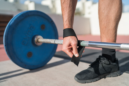 Weightlifting wrist straps support for bodybuilding and powerlifting. Fitness man wearing accessory during barbell weight lifting deadlift exercise workout at gym. Closeup of hand and bar.