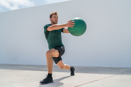 Working out man training legs and core ab workout doing lunge twist exercise with medicine ball weight. Gym athlete doing lunges and torso rotations for abs training.