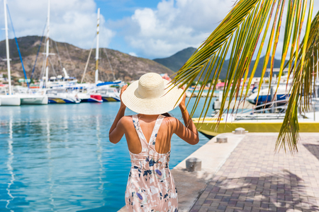 Young woman with sun hat in Philipsburg marina harbor, St Maarten, popular port of call for cruise ship travel destination. Netherlands Antilles, tropical summer vacation.