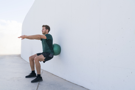 Strength training man doing squats using medicine ball rolling on wall squatting at fitness centre. Workout squat bodyweight exercises using medicine ball. Fitness athlete working out. Stock Photo