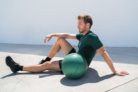 Fit athlete man relaxing at fitness gym during medicine ball workout. Healthy and active lifestyle young adult portrait.