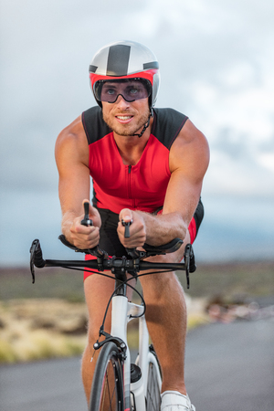 Professional cyclist biking on road bike training for triathlon competition on road bicycle in Hawaii. Triathlete working out outdoors. Man sport athlete. Stockfoto
