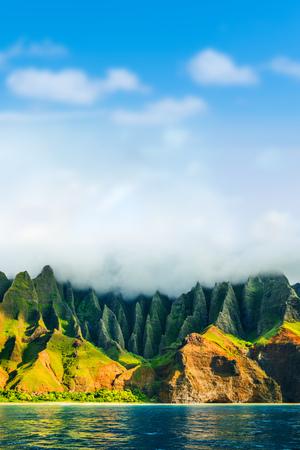Costa di Na Pali, Kauai, Hawaii vista dal tour in crociera al tramonto sul mare. Paesaggio della costa della natura nell'isola di Kauai, Hawai, USA Viaggio alle Hawaii. Copi lo spazio su cielo blu con il fondo delle nuvole.