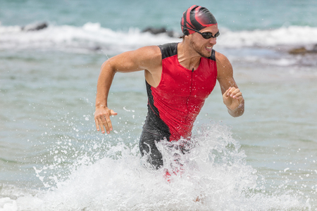 Triathlon swimming man. Male triathlete swimmer running out of ocean finishing swim race. Fit man ending swimming sprinting determined out of water in professional triathlon suit training for ironman. Stock Photo