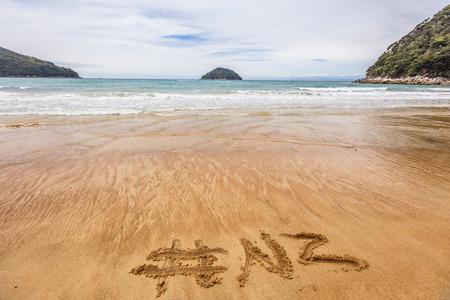 Word NZ hashtag written in sand on New Zealand beach for social media following online advertisement concept. Abel Tasman National Park beach, South Island, New Zealand.