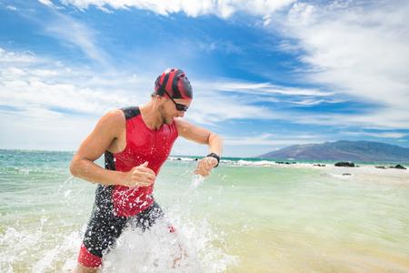 Smartwatch triatlón natación deporte hombre terminando nadar comprobando la frecuencia cardíaca en reloj inteligente. Nadador triatleta macho corriendo fuera del océano. Atleta profesional en entrenamiento de traje de triatlón para ironman. Foto de archivo