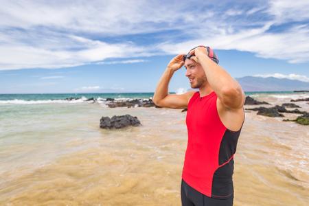 Man triathlete swimmer putting on swim goggles - Triathlon sport athlete going swimming getting ready an ocean swim. Fit man in professional triathlon suit training for ironman. Stock Photo