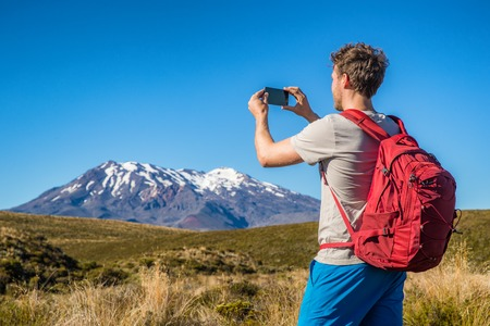 Tourist hiker man taking picture with phone of mountains in New Zealand during hike on Tongariro Alpine crossing track in New Zealand, NZ. Travel tramping lifestyle. Banque d'images