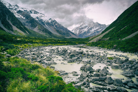 Hooker Valley Track hiking trail, New Zealand. River leading to Hooker lake with glacier over view of Aoraki Mount Cook National Park with snow capped mountains landscape. Summer nature. Stock Photo - 96290947