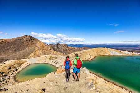 New Zealand popular tourist hiking hike in Tongariro Alpine Crossing National Park. Tramping trampers couple hikers walking on famous destination in NZ. Фото со стока