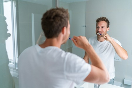 Man getting ready in the morning doing hygiene routine brushing his teeth looking in mirror of home bathroom using toothbrush in for clean dental oral care.