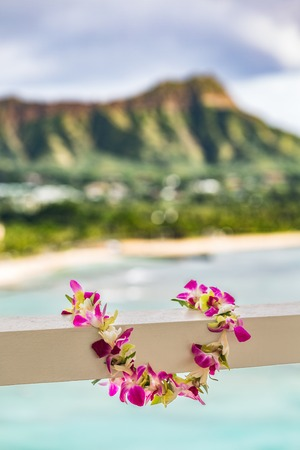 Hawaii travel background. Hawaiian lei flower necklace at holiday resort for luau Hula party with Waikiki beach Honolulu mountain landscape. Real plumeria flowers, polynesian culture.
