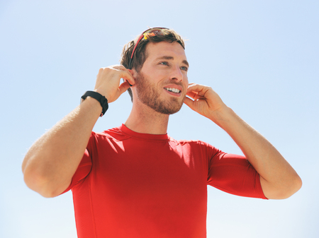 Young man putting on wireless headphone bluetooth connected to smartwatch earphones for fitness run outdoors. Happy active person wearing earbuds for exercise. Stockfoto