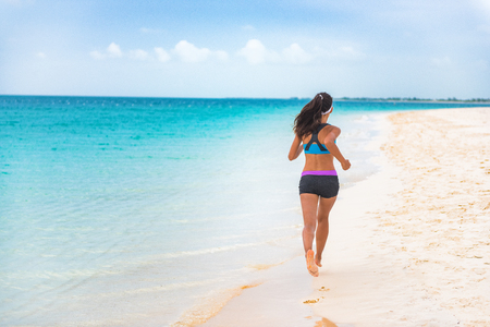 Fitness sports athlete woman runner jogging on Caribbean beach vacation destination. Running girl living an active and fit lifestyle on holiday. Cellulite weight loss concept.