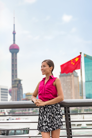 Chinese business woman portrait in Shanghai city by the Bund with the Oriental Pearl tower and China flag in the background. Asian girl in Asia travel..