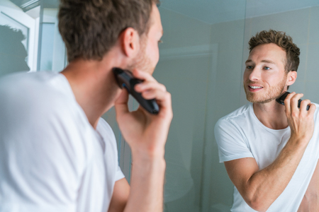 Shaving beard with electric shaver in bathroom. Man looking in mirror, male beauty care routine lifestyle.
