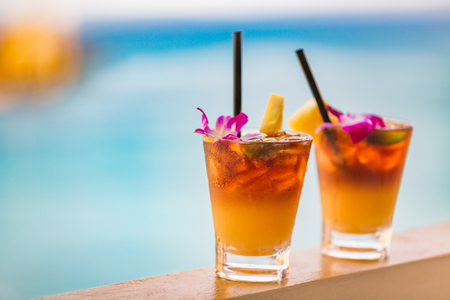 Hawaii mai tai drinks on waikiki beach swimming pool bar travel vacation in Honolulu, Hawaii. Alcohol cocktails with ocean view, luau party nightlife at club.