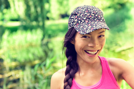 Young happy healthy Asian girl smiling to the camera. Chinese Caucasian multiracial woman wearing fashion cap and hair braid in summer park green grass background. Natural beauty. Stock Photo