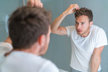 ジェルでバスルームミラースタイリングヘアスタイルのヘアスタイルを見て、または脱毛や灰色の髪をチェックする脱毛男。不幸な男性の健康問題。