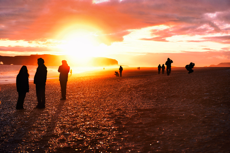 Iceland travel tourists walking on Reynisfjara Black Sand Beach. Landscape photography tourists taking pictures, silhouettes of people against sun flare at sunset. Stock Photo
