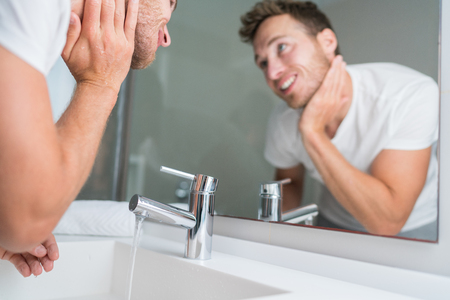 Man washing face in sink in bathroom rinsing after shaving. Home lifestyle copyspace. Stock Photo