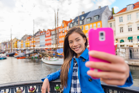 Selfie tourist girl taking photo with phone at Copenhagen Nyhavn, famous Europe tourism attraction. Asian woman visiting the old town waterfront water canal in Kobenhavn, Denmark, Scandinavia. Stock Photo