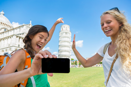 Travel tourists friends selfie at Pisa having fun posing for mobile phone picture. Two girls backpacking on Europe summer vacation taking photo with phone at famous touristic landmark with funny pose.
