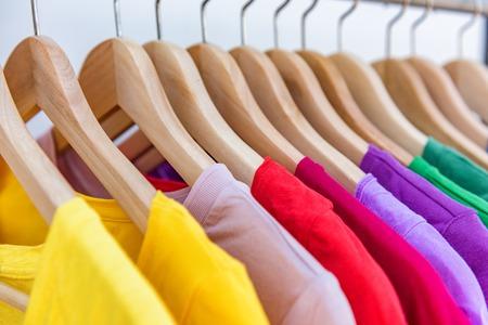 Ropa de moda colgada en el estante de ropa - brillante selección colorida de armario de ropa. Elección del color del arco iris de trajes de moda para niñas en perchas en el armario de la tienda. Limpieza de primavera armario de casa. Foto de archivo