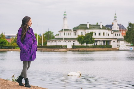 Woman in purple trench coat walking in city park relaxing on weekend. Person enjoying lake view in Copenhagen, Denmark. Spring lifestyle activity, people outside.