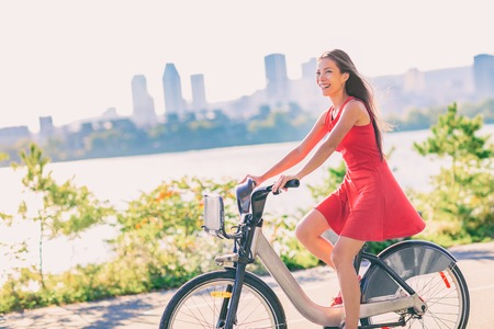 City bike young woman biking riding bicycle in street outdoors in summer with city skyline. Happy multiracial Asian girl active living a healthy lifestyle. Urban living, commute going to work. Stock Photo
