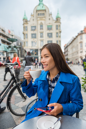 Cafe woman drinking cappuccino coffee at outdoor street terrace in European city. Europe travel lifestyle. Asian businesswoman in blue trench coat working texting sms on mobile phone.