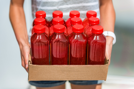 Beet juice red smoothie juicing bottles box of cold pressed vegetable juices. Woman holding delivery box. Health trend for cleansing of organic raw juices. Juicing for diet cleansing detox.