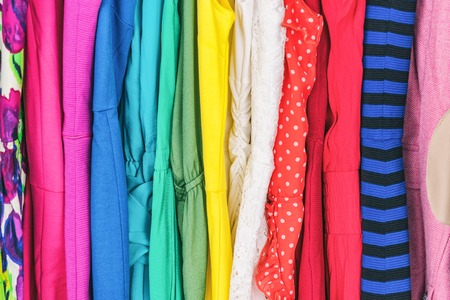 Closet womens fashion outfits clothes arranged in rainbow colors assorted. Clothing store dresses hanging on shopping rack. Variety of fabrics and patterns, wool, polyester, polka dots, stripes.