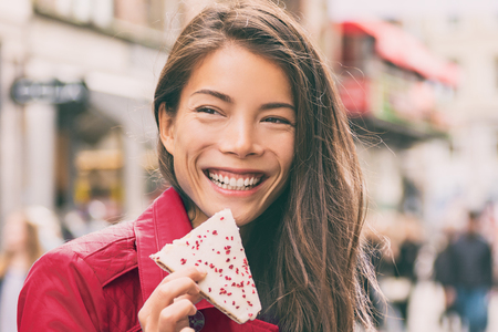 Asian woman eating cookie in city street happy smiling. Girl holding a hindbaersnitte raspberry cake enjoying urban lifestyle. Denmark travel tourist in Copenhagen.