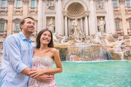 Italy Rome travel tourists couple at Trevi Fountain, European destination vacation. Happy young romantic interracial couple traveling in Europe. Man and Asian woman walking together. Stock Photo
