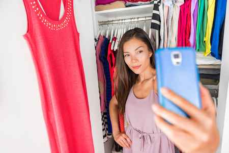 Selfie Asian girl taking photo with phone of outfit in walk-in closet dressing room. Clothes matching style. Shopping girl using smartphone fashion app posting on social media. Stock Photo