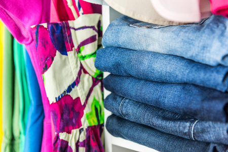 Jeans and clothes in womans closet. Neat organized clothing in walk-in wardrobe with shelves and hangers for clean organization. Spring cleaning organizer, folded colorful outfits.