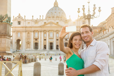 Rome selfie tourists couple by Vatican city and St. Peters Basilica church taking photo with phone. Happy travel woman and man holding cellphone on romantic honeymoon in Italy. Stock Photo