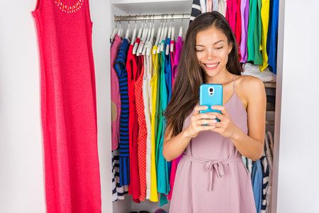 Selfie Asian girl taking photo with phone of outfit in walk-in closet dressing room. Clothes fashion stylist. Shopping girl using smartphone fashion app posting on social media. Stock Photo
