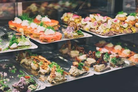 Duński smorrebrod tradycyjne otwarte kanapki w sklepie spożywczym w Kopenhadze. Wiele kanapek na wystawie z owocami morza i mięsem, wędzonym łososiem. Zdjęcie Seryjne